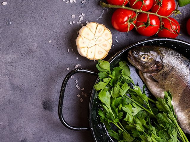 Raw fresh whole fish with vegetables and rice ready to cook. Fresh trout on a pan. Ingredients for cooking on a gray concrete background. Space for text. Diet and healthy food concept. Fish background